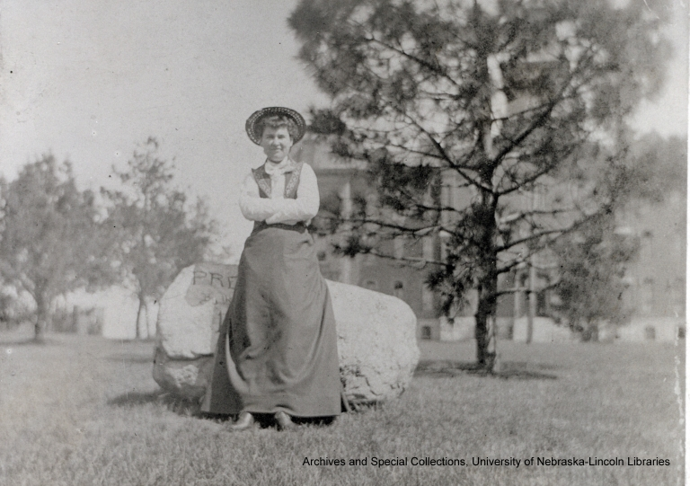 With her arms folded in front of her, Willa Cather stands in front of an engraved boulder on the University of Nebraska campus. ca. 1893 (Bernice Slote, Papers Collection).